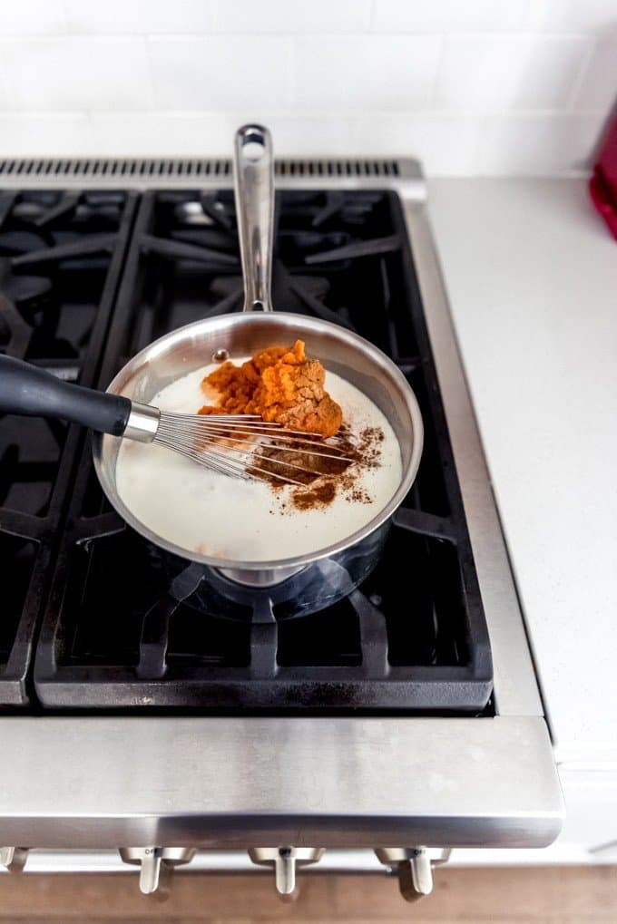 An image of cooked cream and whole milk in a saucepan on the stove with sugar, pumpkin puree, cinnamon, and other spices for a pumpkin panna cotta recipe.