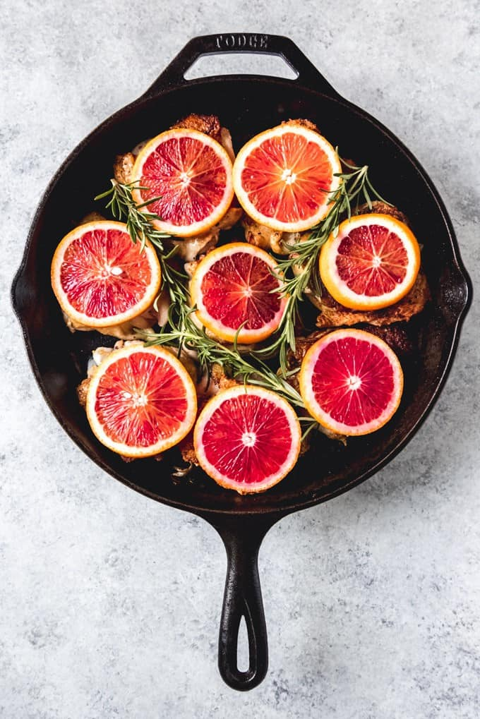 An image of blood orange slices and rosemary sprigs on top of crispy chicken thighs in a cast iron skillet.