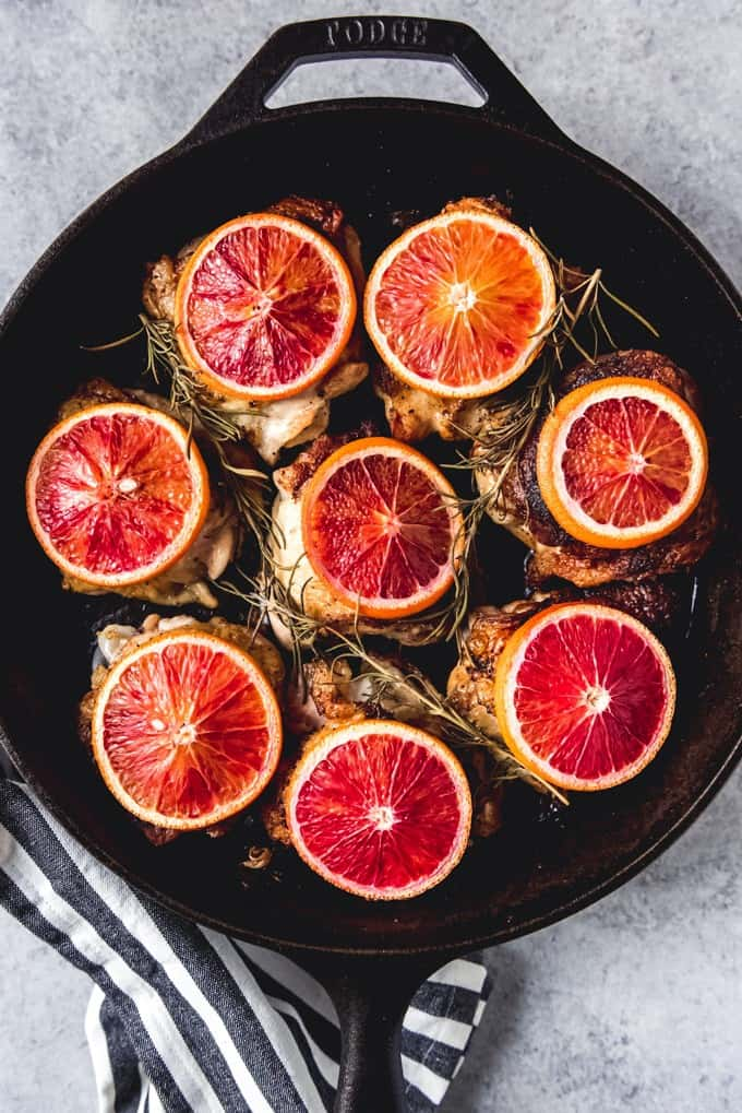 An image of a cast iron pan with crispy chicken thighs topped with slices of blood oranges.