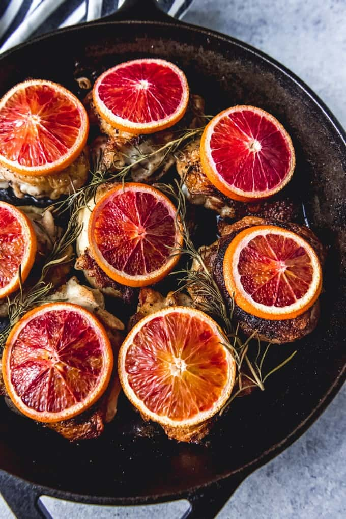 An image of blood orange chicken thighs in a cast iron skillet with slices of blood oranges on top.