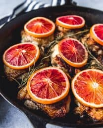 blood orange slices on top of cooked chicken thighs with fresh herbs