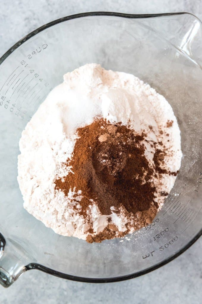 An image of pumpkin pie spice in a bowl with flour and other dry ingredients for making pumpkin spice bread with chocolate chips.