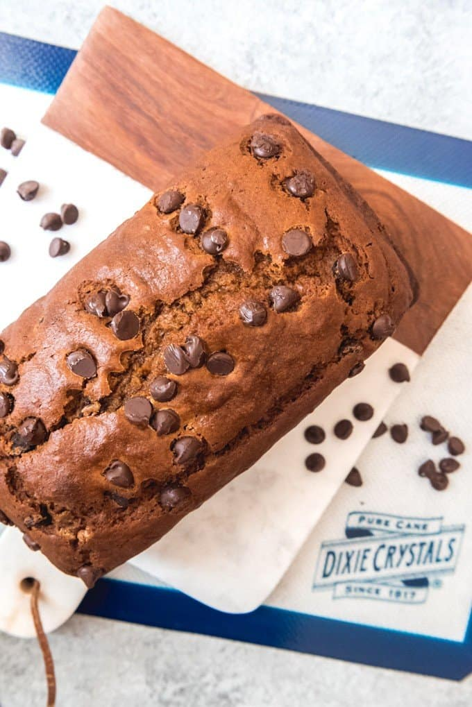 An image of a loaf of pumpkin chocolate chips bread on a cutting board.