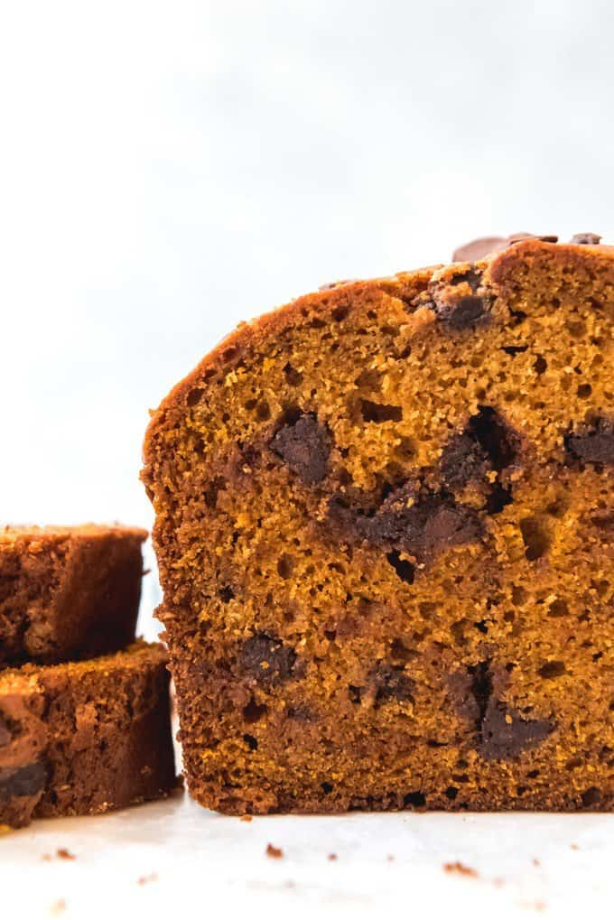 An image of a sliced loaf of pumpkin spice bread studded with chocolate chips.