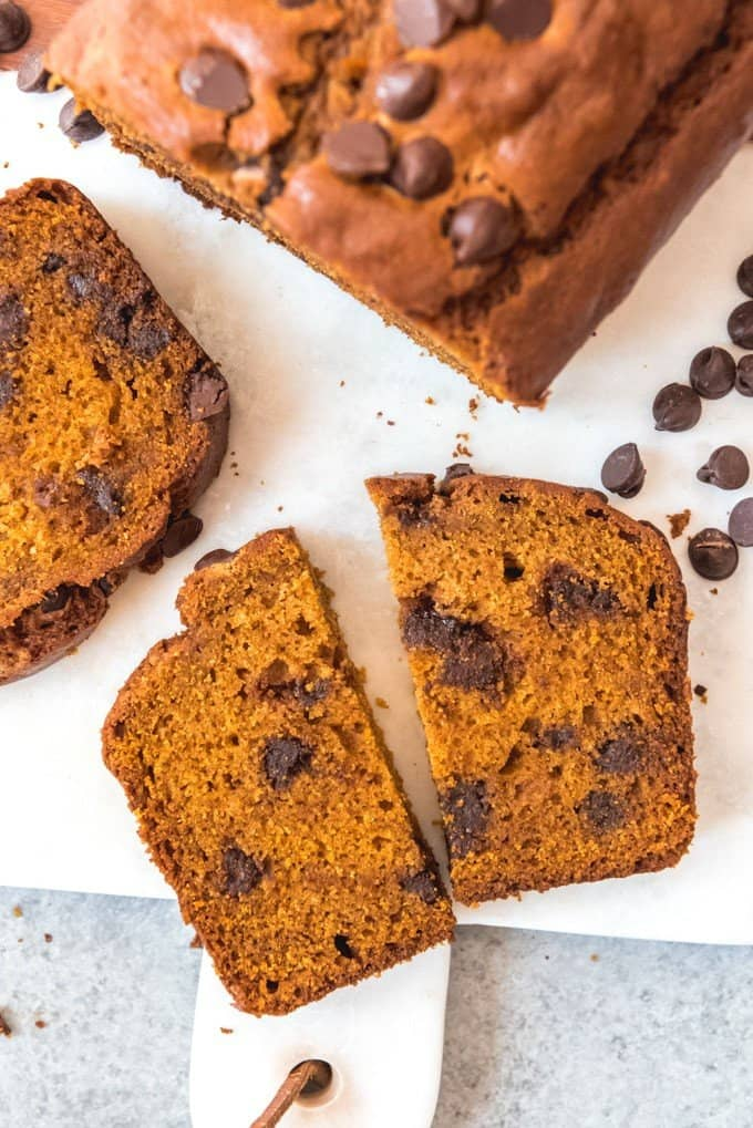 An image of a slice of moist pumpkin bread studded with chocolate chips.