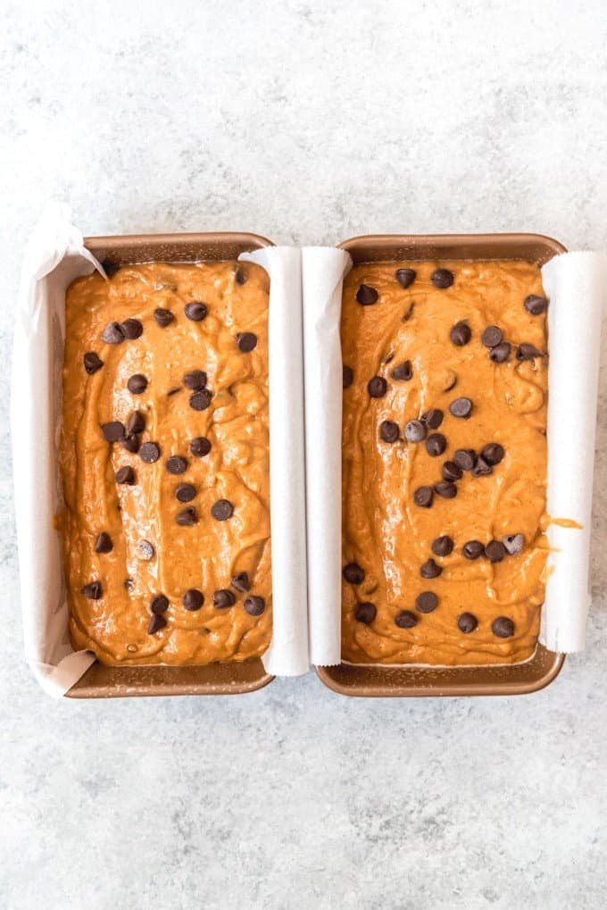 An image of two unbaked loaves of chocolate chip pumpkin bread ready to go into the oven.