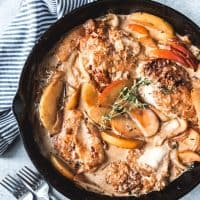 apple cider chicken in a skillet with apple slices