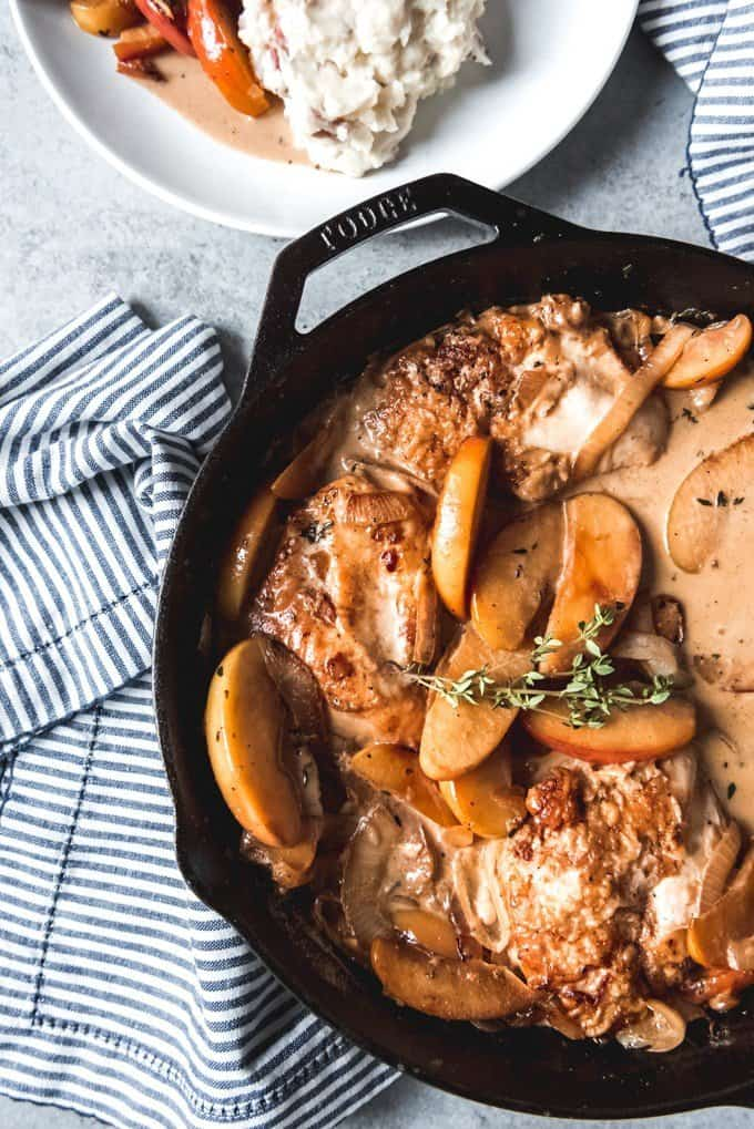 An image of a cast iron skillet with chicken fricassee with apples, onions, and thyme.