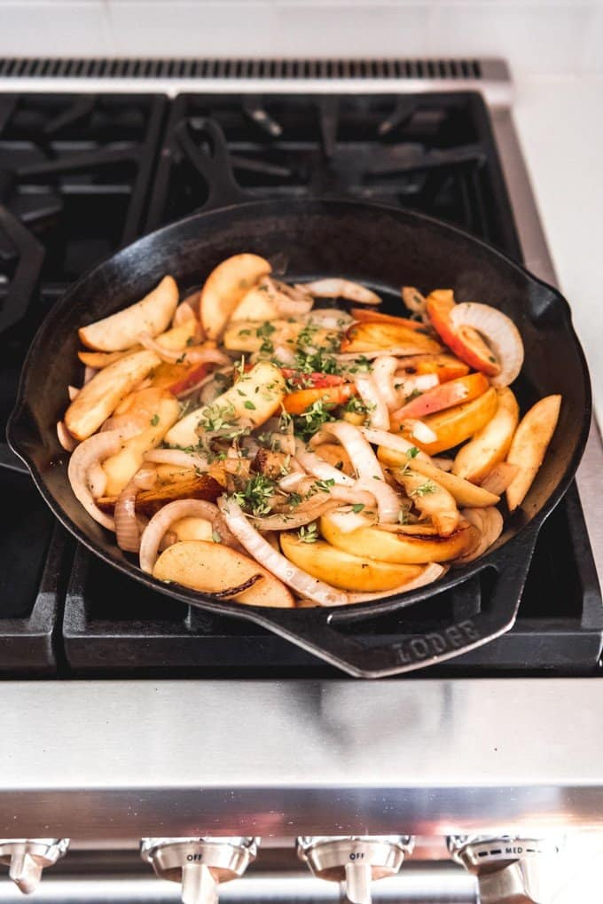 An image of sauteed apples, onions, and thyme in a cast iron skillet on the stove for a chicken skillet meal with apples.