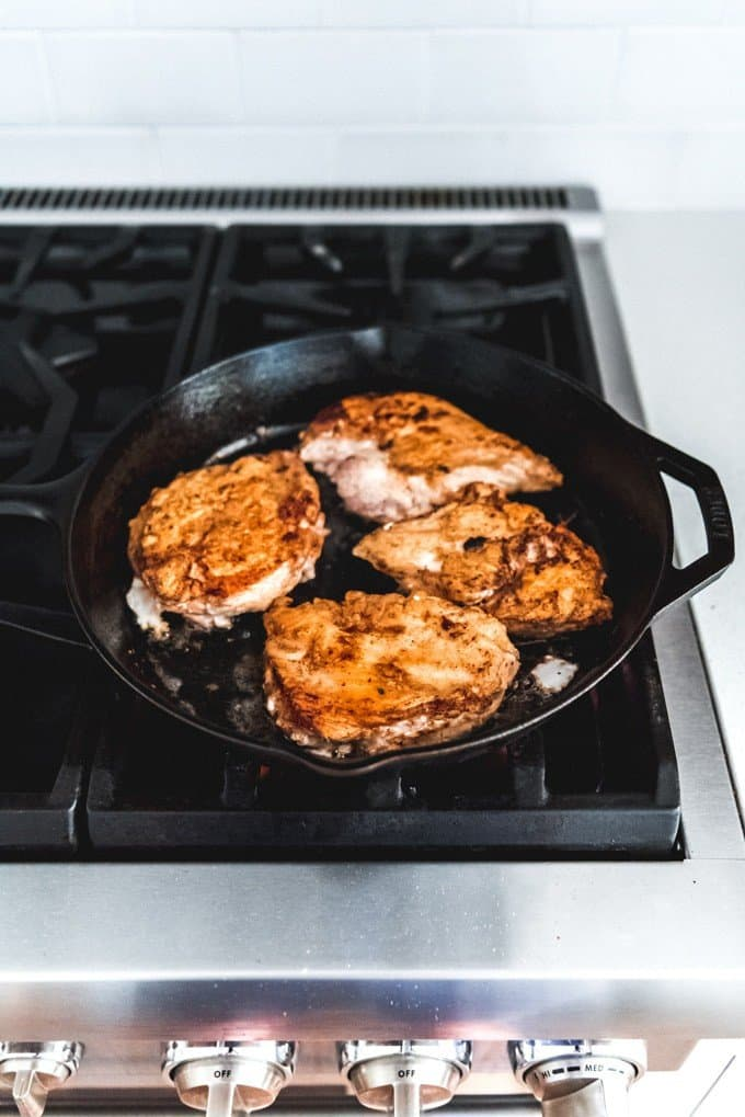 An image of crispy chicken thighs in a cast iron skillet on the stove top.
