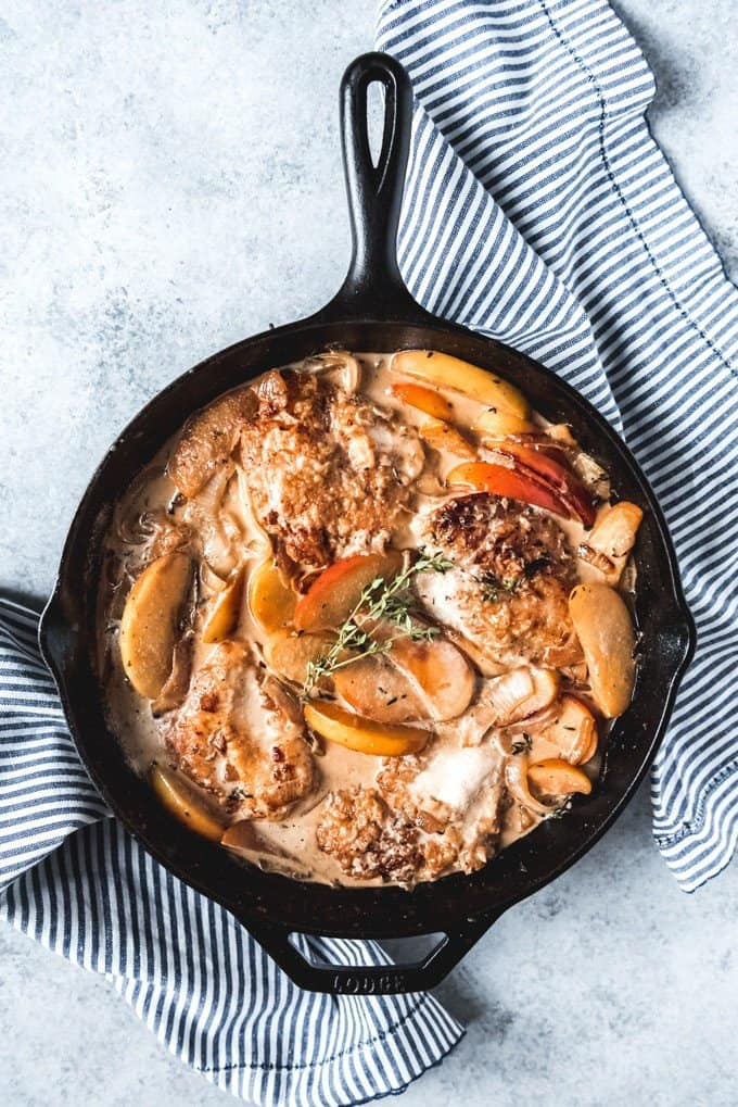 An image of a chicken fricassee with apples in a cast iron skillet makes the best fall dinner recipe!