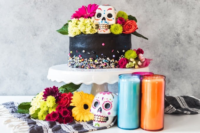 a black buttercream frosted cake on a white cake stand with flowers, colored skulls, and candles
