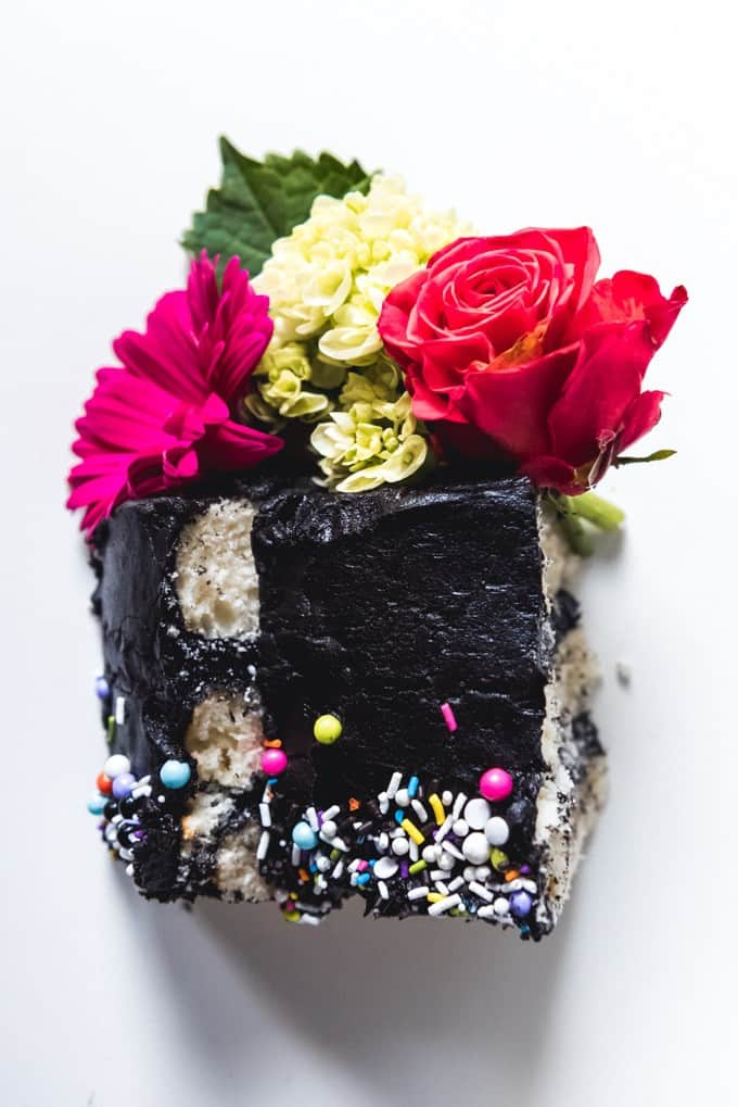 An image of slices of white cake with black buttercream frosting, sprinkles, and fresh flowers decorating the top.