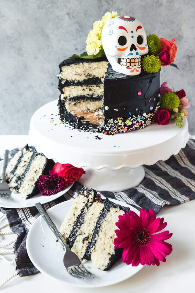 An image of a sliced Dia de los Muertos inspired Halloween cake with black buttercream and three layers of vanilla cake with sprinkles and flowers.