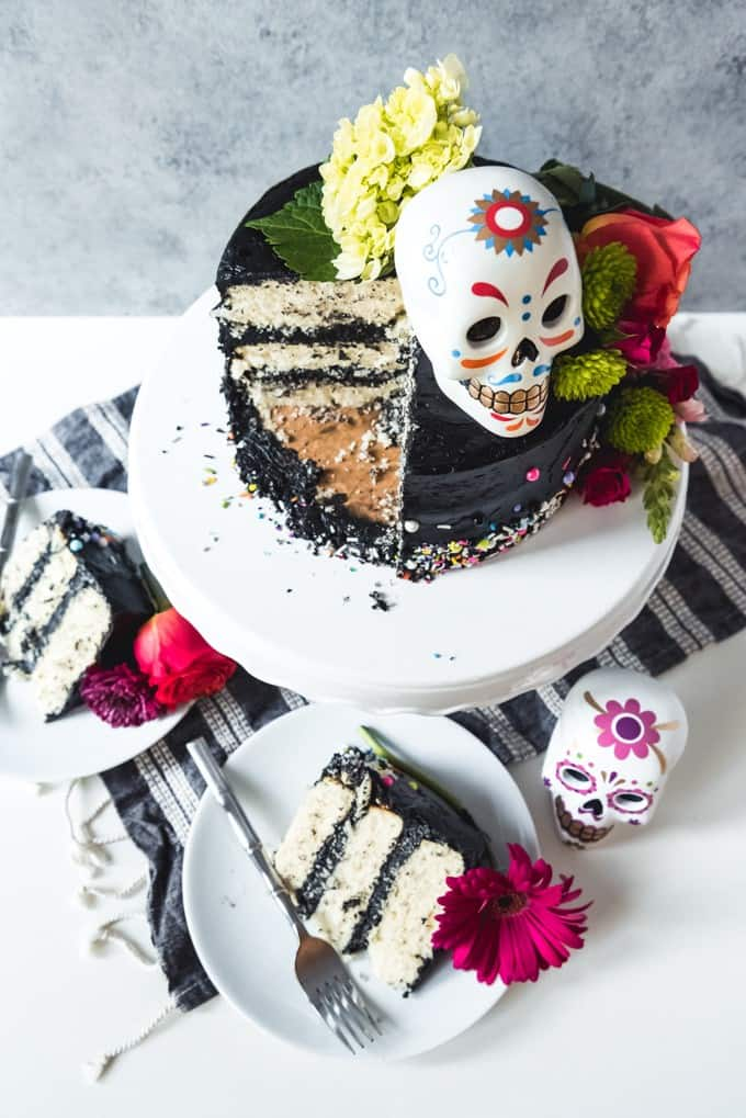 An image of a sugar skull inspired Day of the Dead cake with black buttercream frosting, sliced and ready to serve on plates.