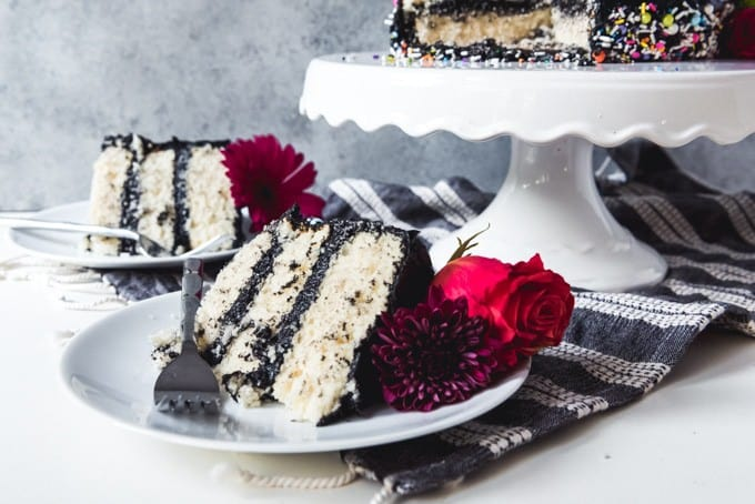 An image of slices of white cake with chocolate buttercream dyed black, laying on their sides on dessert plates with forks and flowers.
