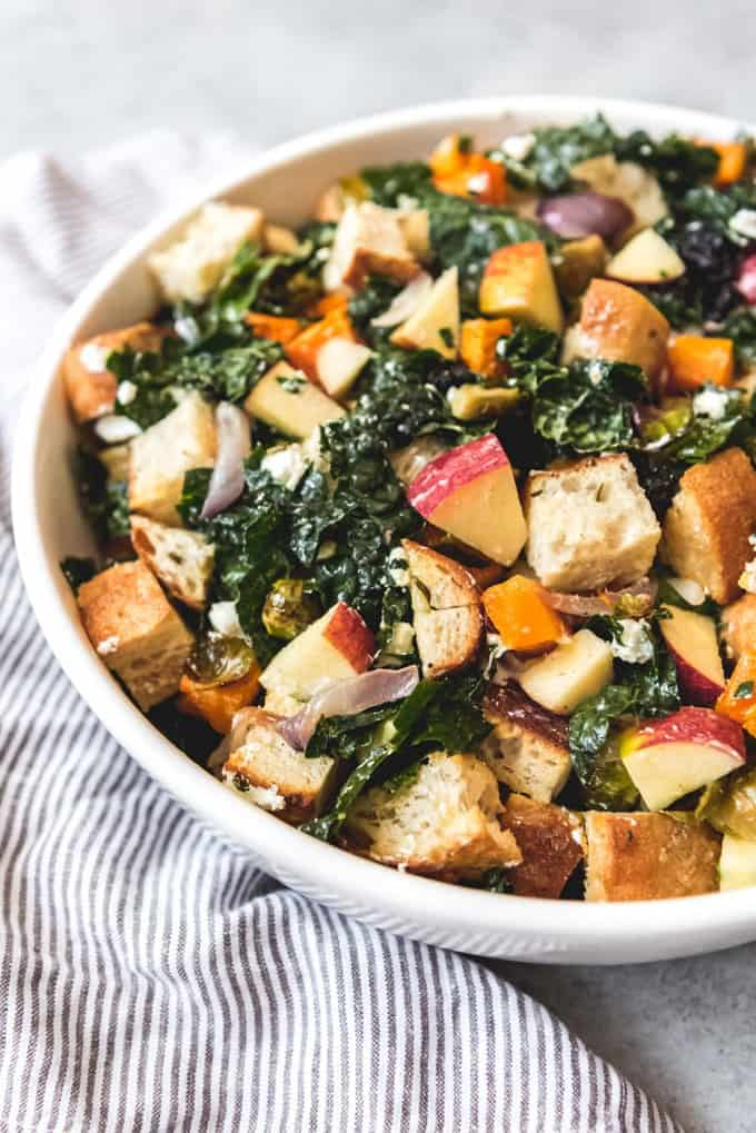 "This wonderful Fall Panzanella Salad features chunks of toasted bread (the name Panzanella comes from the Italian ""pane"" for bread) and seasonal ingredients like kale, roasted brussels sprouts, butternut squash, apples, goat cheese, and more, all dressed in a delicious maple mustard vinaigrette.  It's wonderful as new side dish addition to the Thanksgiving table, or you can eat it as a light dinner or lunch during the Fall!"