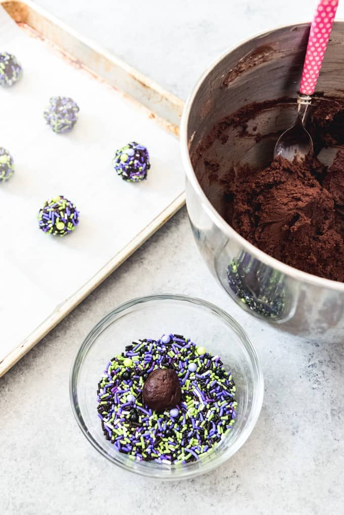 An image of chocolate cookie dough rolled into balls and rolled in purple, green, and black Halloween sprinkles.