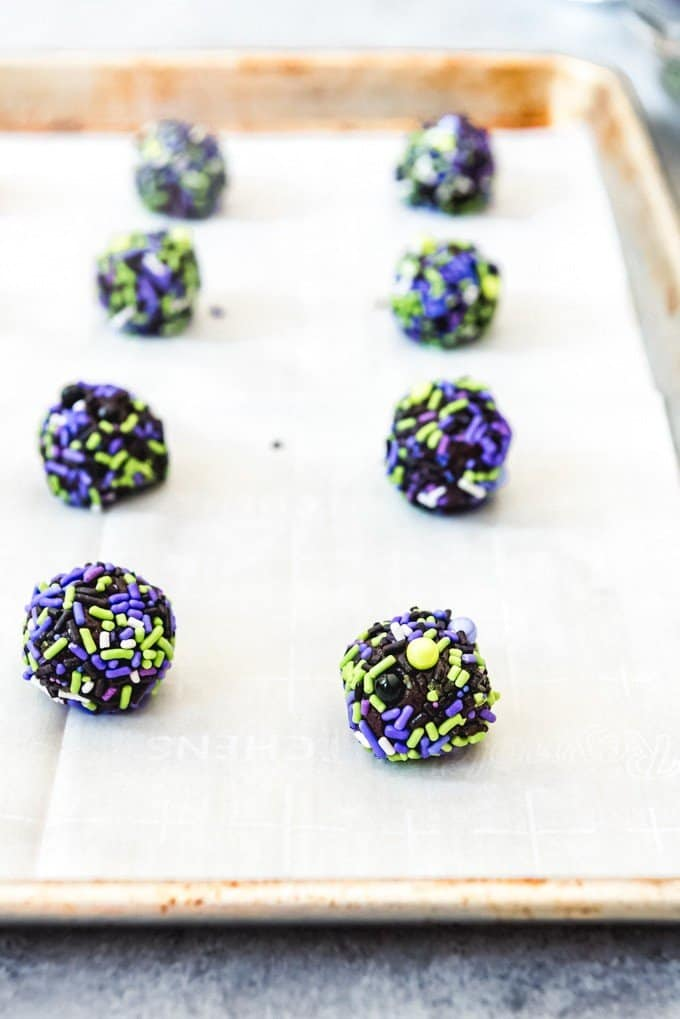An image of sprinkle covered balls of chocolate cookie dough arranged on a parchment paper lined baking sheet.