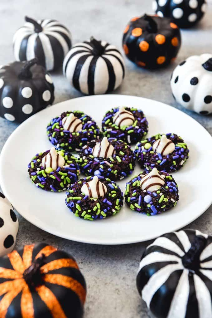 An image of chocolate sprinkle cookies with white chocolate Hershey's Hugs pressed into the centers arranged on a white plate surrounded by Halloween decorations.
