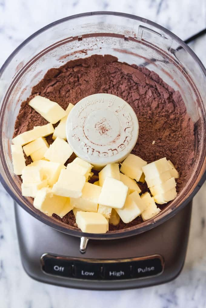 An image of cubed butter with cocoa powder, sugar, flour, and salt in a food processor for making a chocolate pie crust dough.