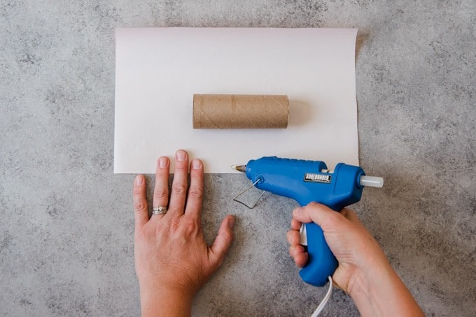 An image of hands holding a blue glue gun being used to put glue on a piece of wrapping paper that will go around an empty cardboard tube for a Christmas cracker.