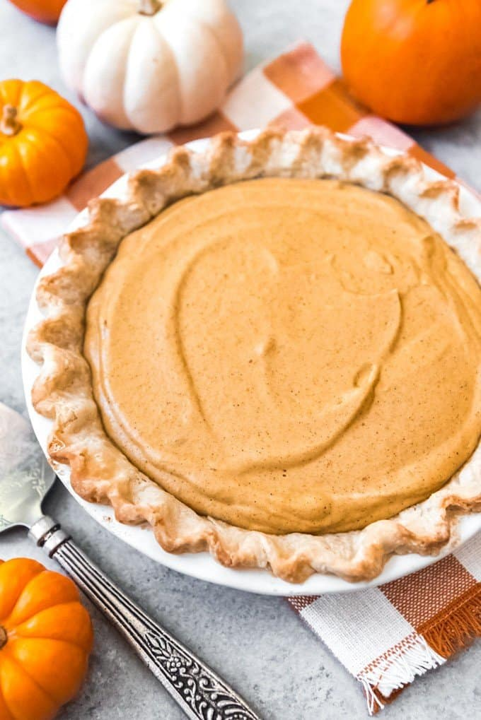 An image of the filling for a pumpkin chiffon pie in a fully blind baked pie crust, ready to be garnished with whipped cream and served for Thanksgiving dessert!