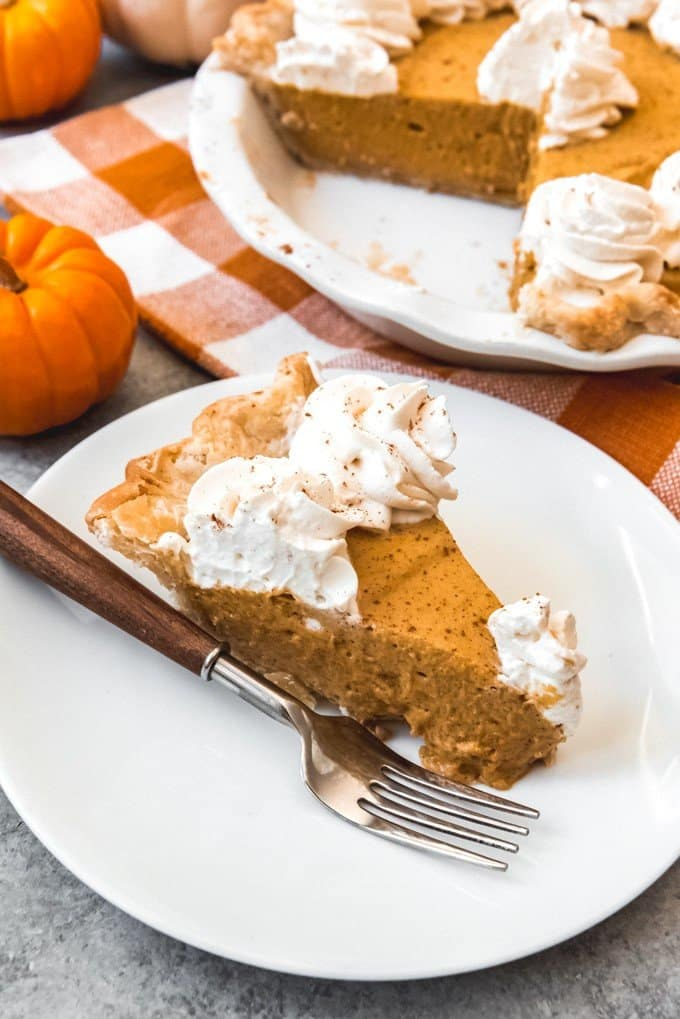 A slice of no-bake pumpkin chiffon pie decorated with whipped cream for Thanksgiving dinner.