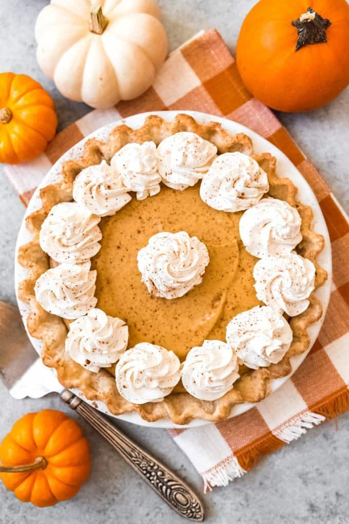 An image of a pumpkin chiffon pie from scratch with swirls of whipped cream and a dusting of ground cinnamon on top.