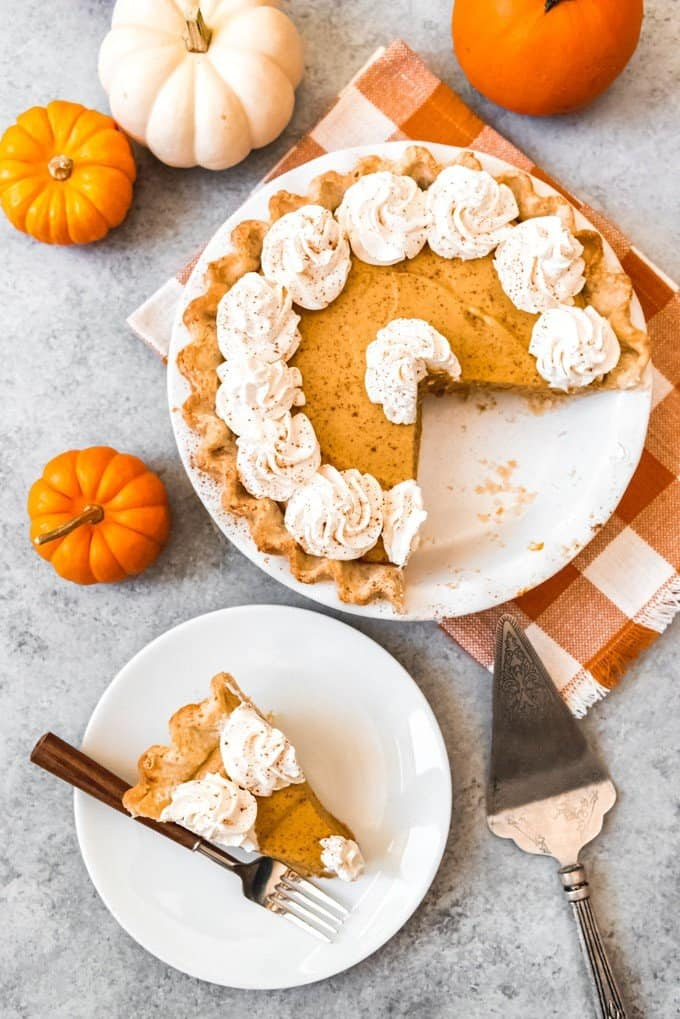 An image of a sliced pumpkin chiffon pie with a serving on pumpkin pie on the plate next to it.