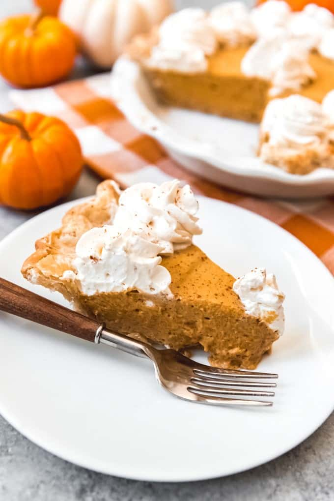A slice of homemade chiffon pumpkin pie on a white plate with a fork with the rest of the pie in the background.