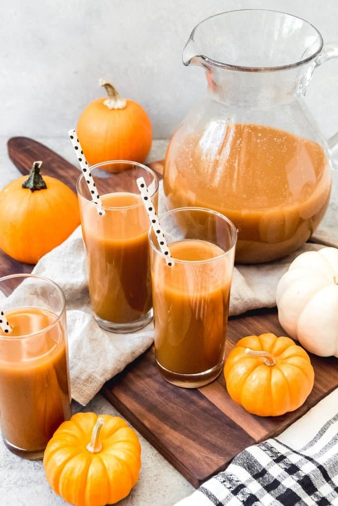 An image of glasses of pumpkin juice with a pitcher of pumpkin juice and miniature pumpkins next to them.