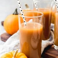 tall glasses filled with pumpkin juice with spotted strawbs inside and pumpkins scattered around