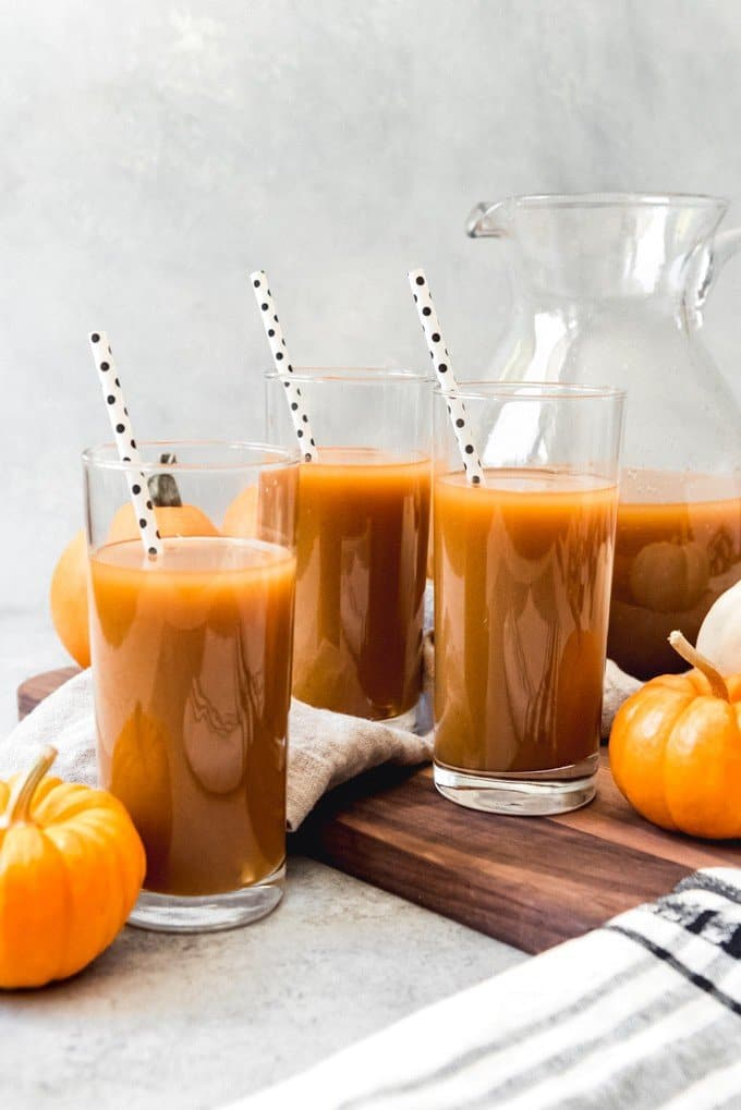 An image of glasses of chilled pumpkin juice made with apple cider, pumpkin puree, and pumpkin spice.