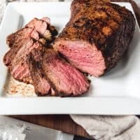 tri tip sliced on a white plate with a knife to the side