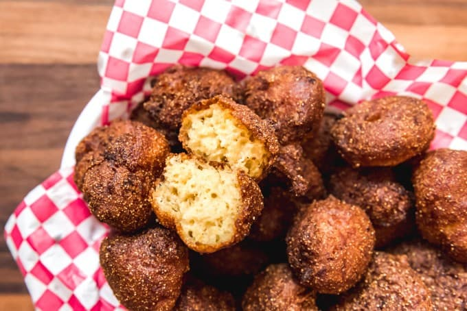 An image of a the soft, fluffy interior of homemade Arkansas hush puppies, fried to a golden brown in hot oil.