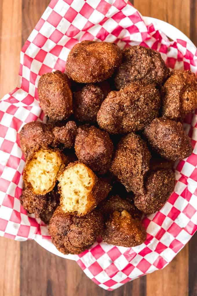 an aerial view of a bowl of southern hush puppies and one split open