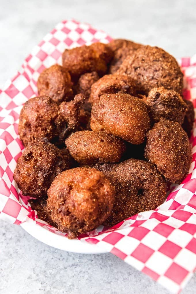 An image of deep fried balls of cornmeal dough known as hush puppies in the South.