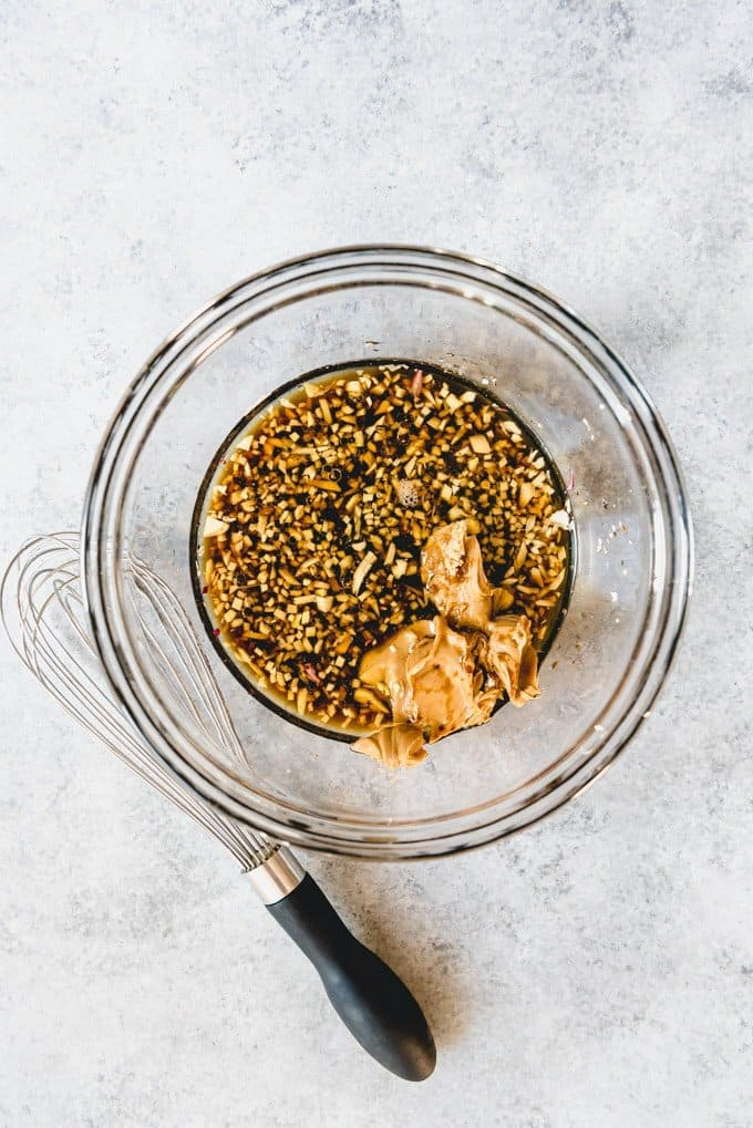 An image of a bowl with soy sauce, sesame oil, peanut butter, minced garlic, and grated ginger for making a ginger peanut Asian dressing for Asian slaw.