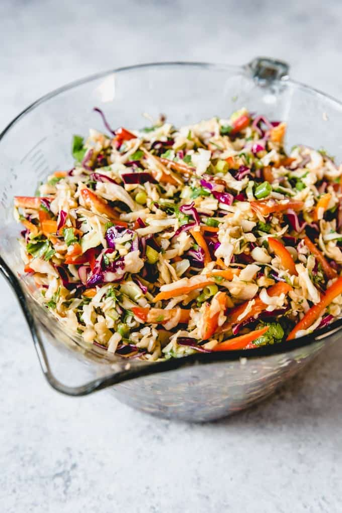 An image of a healthy, crunchy Asian slaw with a Ginger Peanut Dressing in a glass bowl.