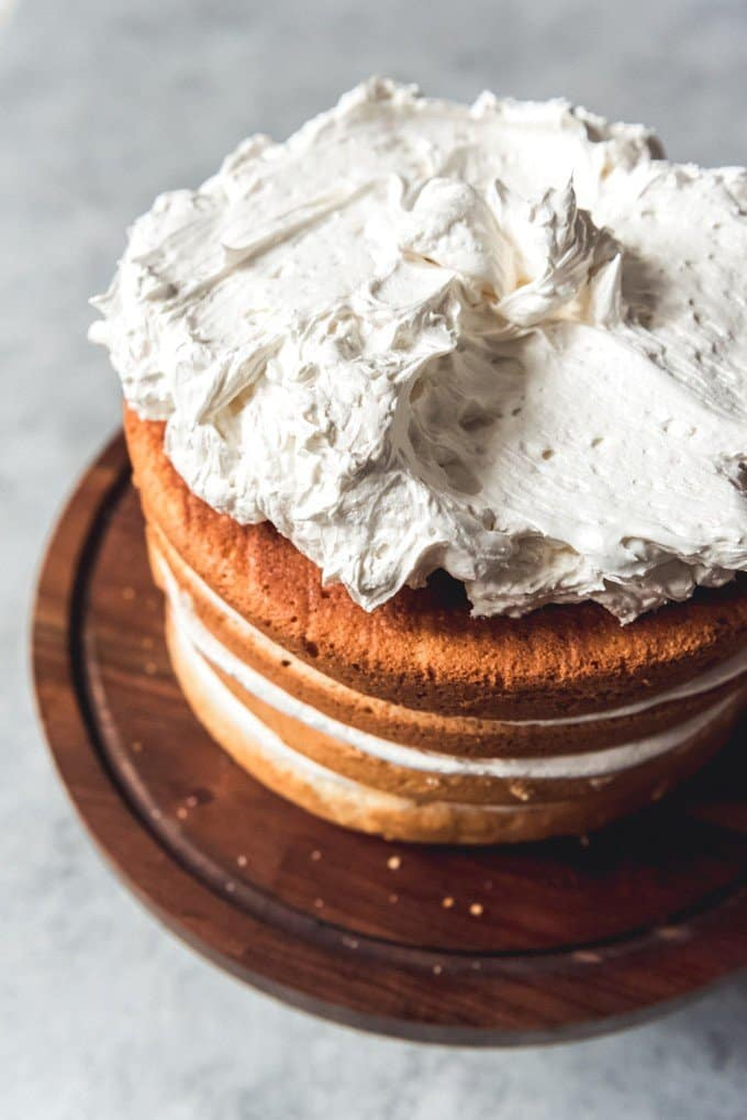 An image of a stacked layer cake with piles of fluffy Swiss meringue buttercream on top.