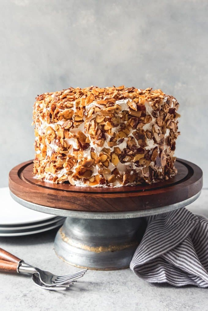 An image of a burnt almond cake on a wood and metal cake stand.