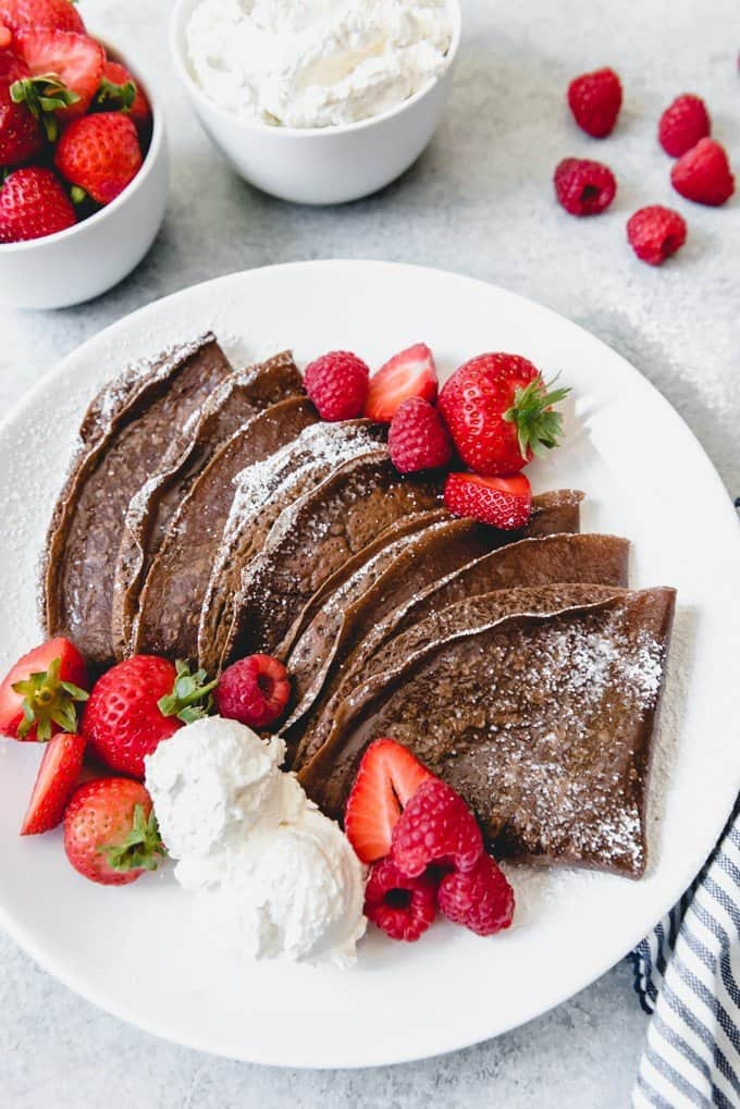 An image of stacked chocolate crepes on a plate with fresh strawberries and raspberries for filling the crepes.