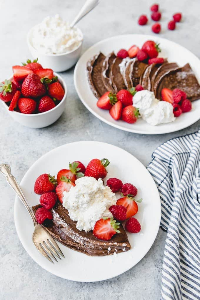 An image of chocolate crepes with strawberries, raspberries, and freshly whipped cream.