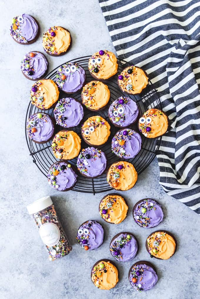 An image of chocolate Halloween Lofthouse sugar cookies decorated with sprinkles and orange and purple frosting.