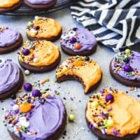 purple and orange frosted chocolate sugar cookies topped with sprinkles