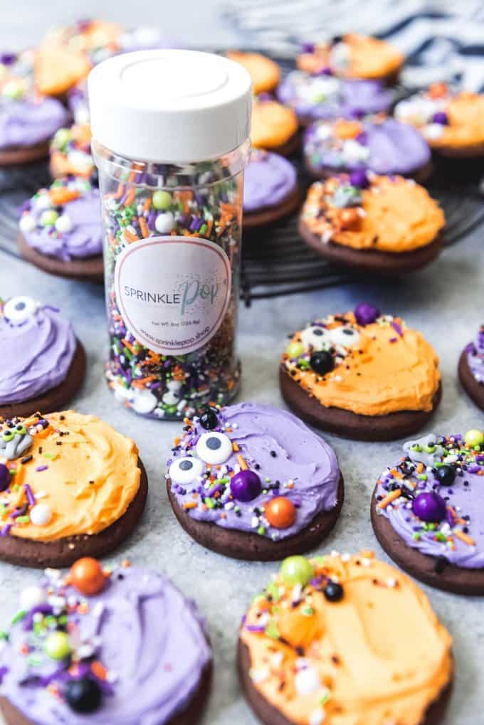 An image of chocolate Lofthouse cookies frosted with purple and orange frosting for Halloween and sprinkled with monster mash sprinkle mix from Sprinkle Pop.