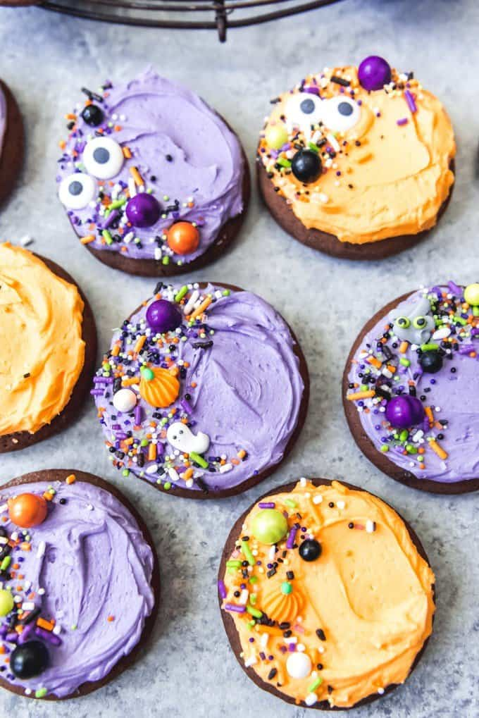 An image of purple and orange frosted chocolate sugar cookies decorated with Halloween sprinkles.