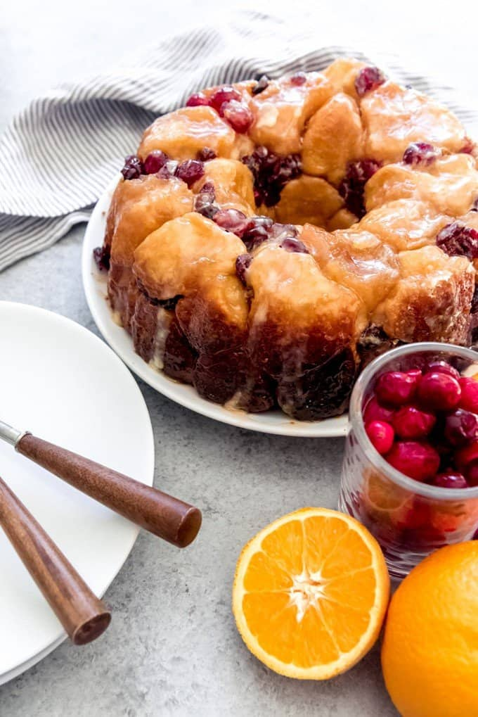 An image of a gorgeous, glazed loaf of cranberry orange pull apart monkey bread with sliced oranges and fresh cranberries next to it.
