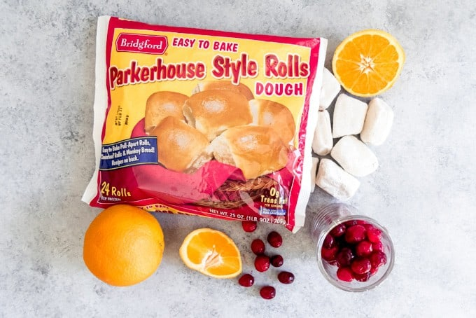 An image of Bridgford Parkerhouse Style Frozen Rolls Dough with fresh cranberries and orange for making cranberry orange pull apart monkey bread.